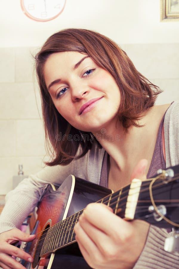 Ung kvinna för härlig brunett med en gitarr royaltyfria bilder
