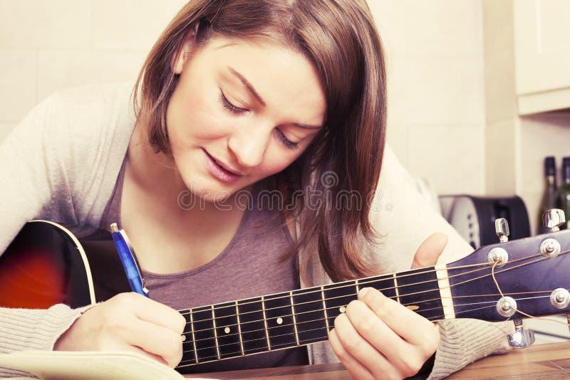 Ung kvinna för härlig brunett med en gitarr fotografering för bildbyråer