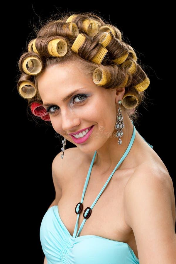 Ung kvinna för härlig flört med hårrullar som isoleras på svart arkivbilder