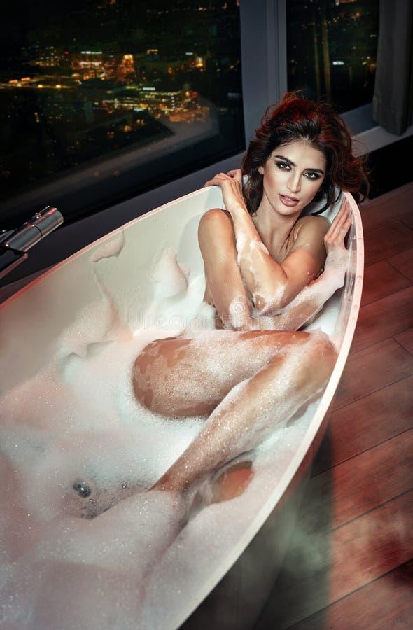 Ung kvinna för härlig och sexig brunett i en bubbelbad arkivfoto