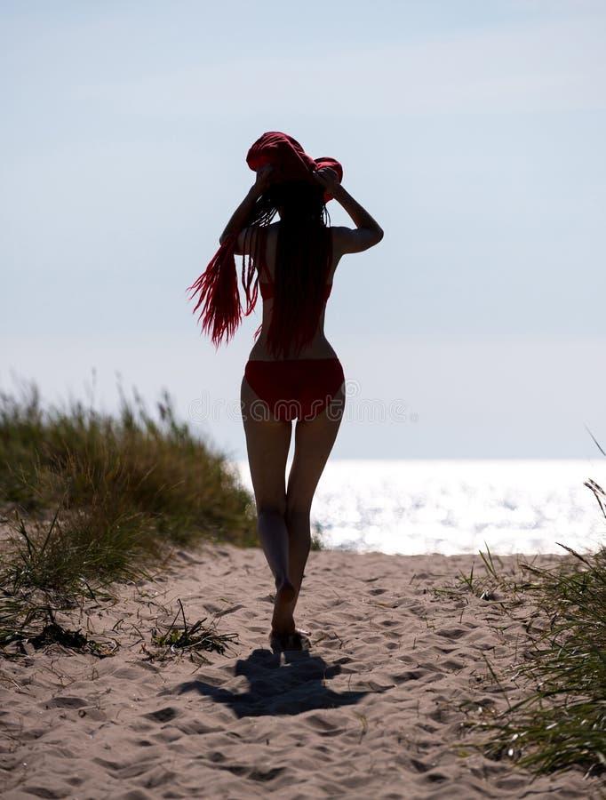 Ung kvinna för härlig rödhårig man i röd baddräkt arkivbilder