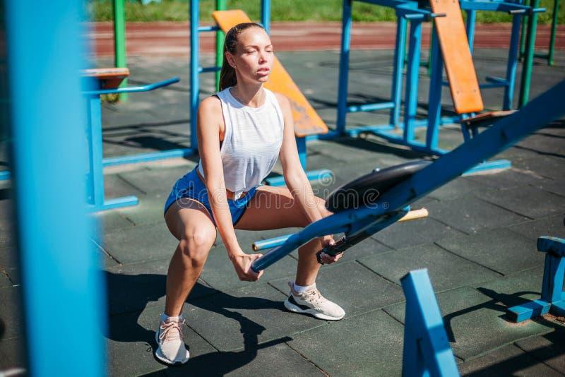 Ung kvinna för idrotts- sportar som gör övningar på sportfält med simulatorer fotografering för bildbyråer