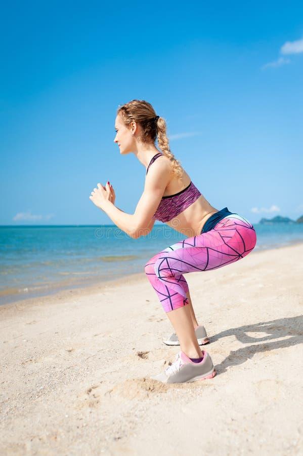 Ung kvinna för kondition som utarbetar kärna och glutes med bodyweightgenomköraren som gör satta övningar på stranden royaltyfria bilder
