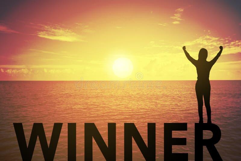 Ung kvinna för kontur som upp står och lyfter hennes hand om vinnarebegrepp på vinnaretext över en härlig solnedgång eller solupp arkivfoto