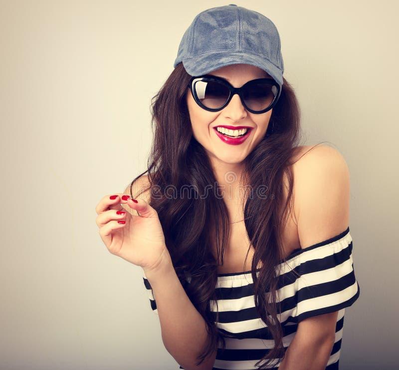 Ung kvinna för lycklig njutning i solexponeringsglas och blå baseballmössa royaltyfria bilder