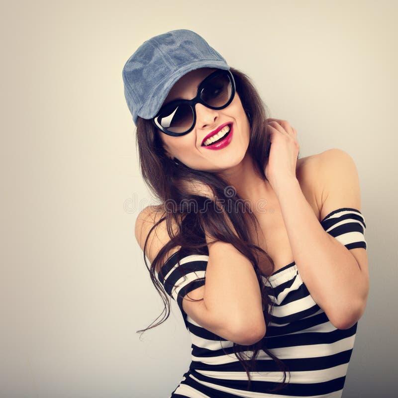 Ung kvinna för lycklig njutning i solglasögon och blå baseballmössa arkivbilder