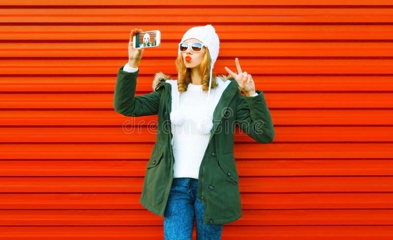 Ung kvinna för mode som tar selfie vid smartphonen på rött arkivfoto