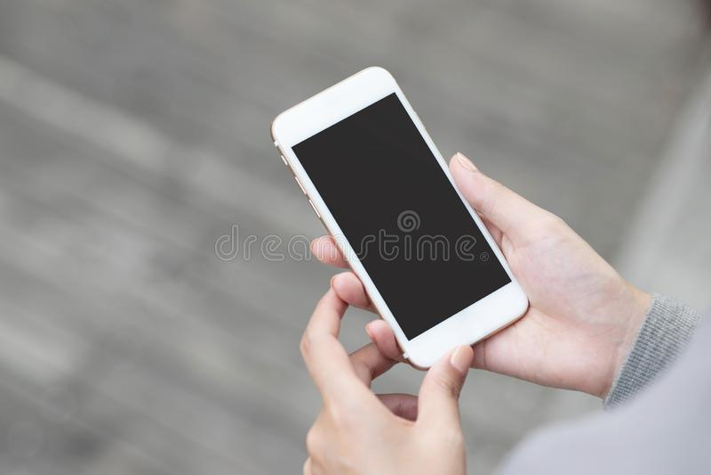 Ung kvinna för nära övre hand i hållande ögonen på meddelande på den mobila smarta telefonen under avbrott använda mobiltelefoner arkivbild
