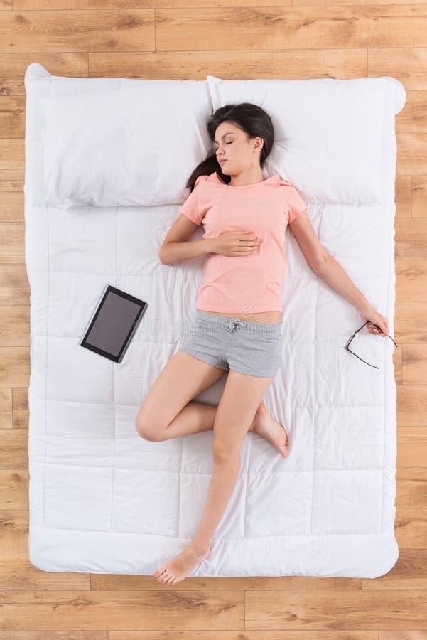 Ung kvinna för nedskärning som sover på säng royaltyfri foto