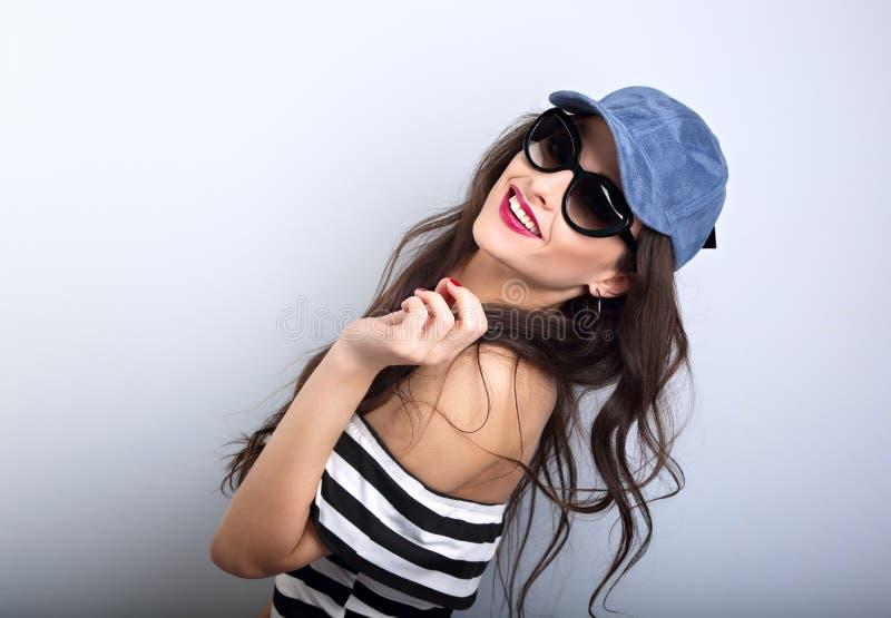 Ung kvinna för njutning i solglasögon och blått posera för baseballmössa arkivbild