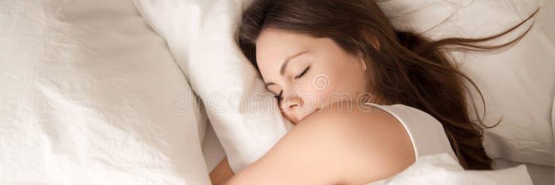 Ung kvinna för ovannämnd panoramautsikt som sover i säng som kramar kudden fotografering för bildbyråer
