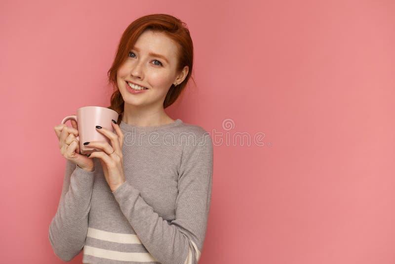 Ung kvinna för rödhårig man med leenden för en kopp som ser kameran royaltyfria bilder