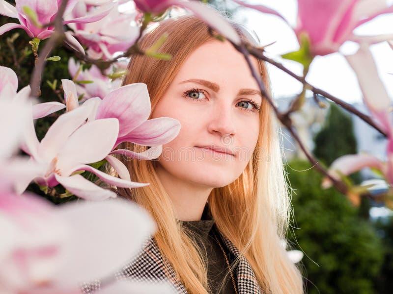 Ung kvinna för skönhet som tycker om naturen i vårmagnoliaträdgård Romantisk modemodell i blomningblommastående royaltyfri foto