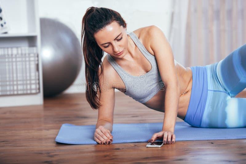 Ung kvinna för slank kondition som hemma gör övning med smartphonen fotografering för bildbyråer