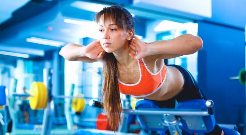 Ung kvinna för sportar som gör övningar på instruktörbaksidamaskinen i idrottshallen royaltyfri bild