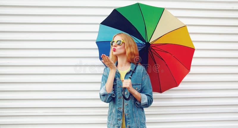 Ung kvinna för stående som rymmer det färgrika paraplyet som blåser röda kanter som överför den söta luftkyssen på vit väggbakgru arkivfoto