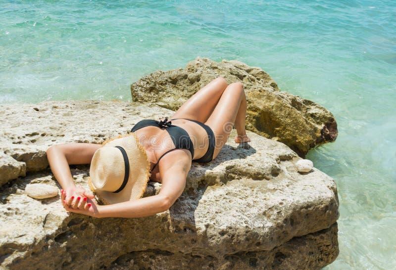 Ung kvinna för tillbaka sikt i svart baddräkt- och sugrörhatt på den lösa snonestranden med det rena havet arkivfoto