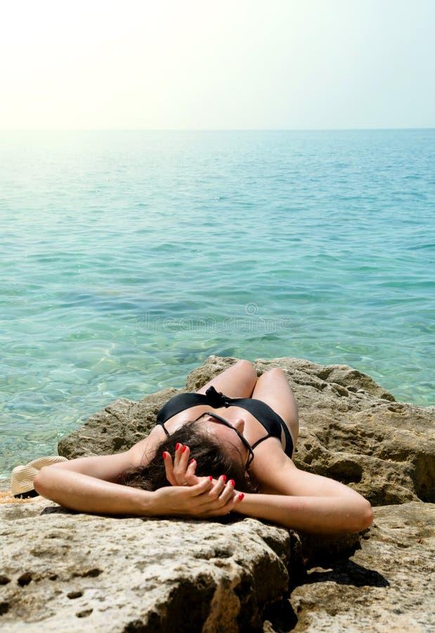 Ung kvinna för tillbaka sikt i svart baddräkt- och sugrörhatt på den lösa snonestranden med det rena havet fotografering för bildbyråer