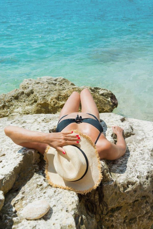 Ung kvinna för tillbaka sikt i svart baddräkt- och sugrörhatt på den lösa snonestranden med det rena havet arkivfoton
