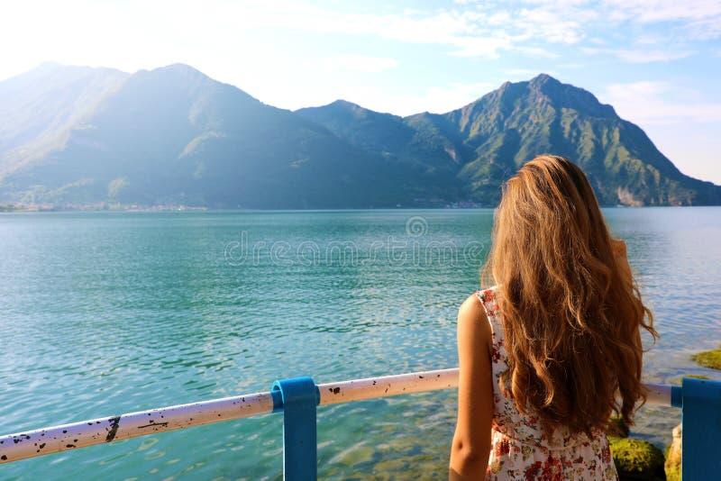 Ung kvinna för tillbaka sikt med klänningen som framme ser härligt sjölandskap av henne kopiera avstånd royaltyfri fotografi