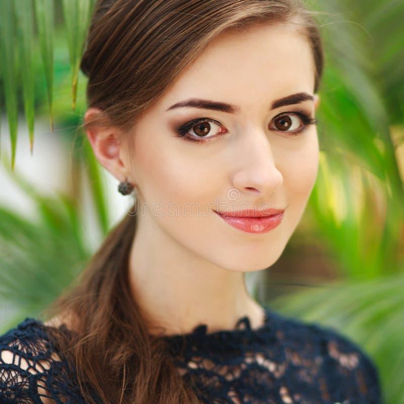 Ung kvinna för trevlig brunett, på bakgrund av sommargräsplanlövverk royaltyfria bilder