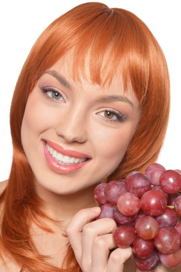 Ung kvinna f?r h?rlig r?dh?rig man med att posera f?r r?da druvor som isoleras p? vit bakgrund royaltyfria foton