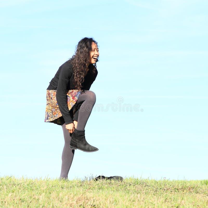 Ung kvinna - flicka som sätter på skor på äng royaltyfri bild