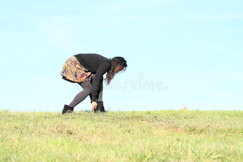 Ung kvinna - flicka som sätter på skor på äng arkivbild