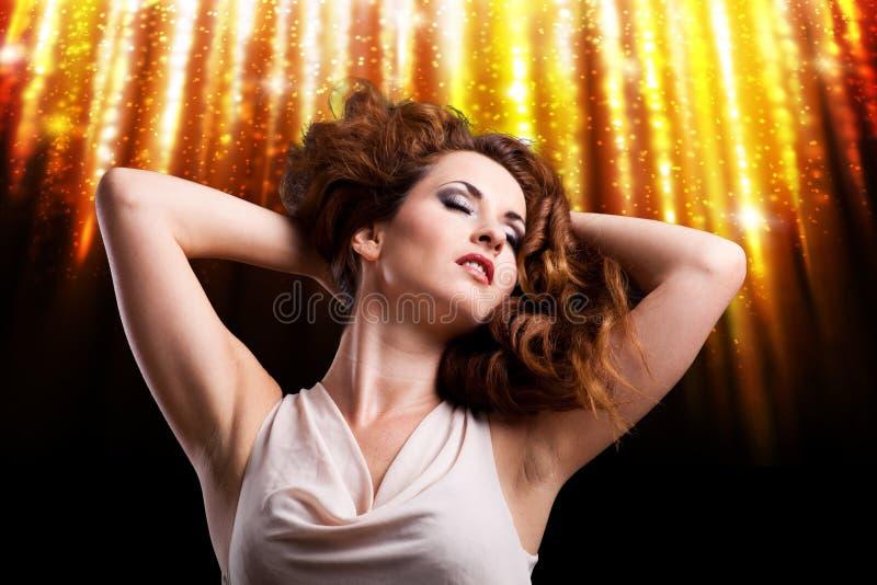 Ung kvinna framme av en fyrverkeribakgrund arkivfoto