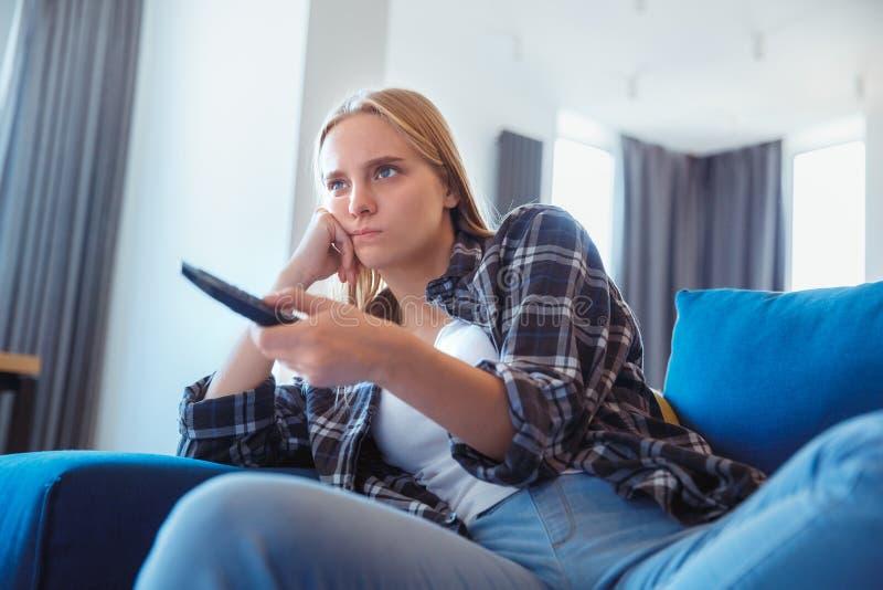 Ung kvinna hemma i den borrade hållande ögonen på tv:n för vardagsrum royaltyfria bilder