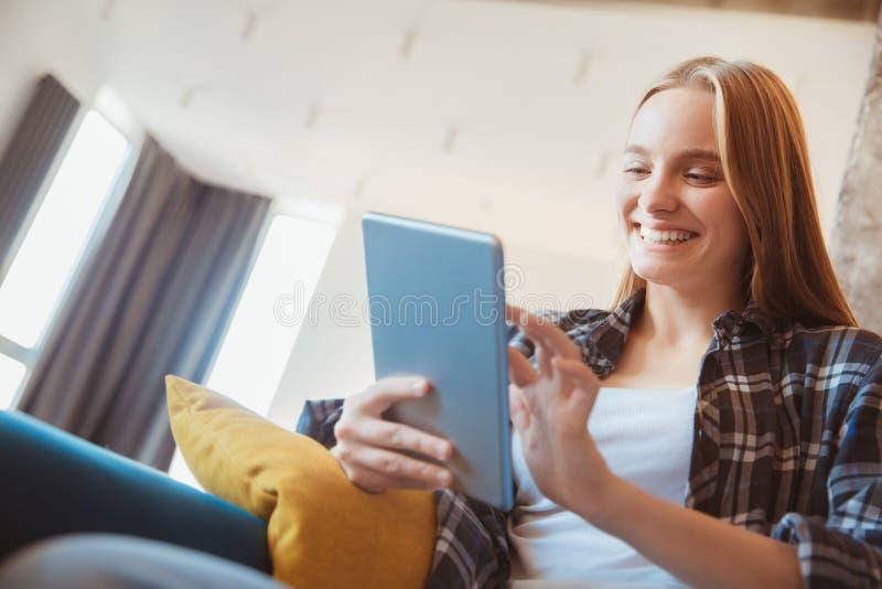 Ung kvinna hemma i vardagsrummet genom att använda digital minnestavlanärbild arkivbild