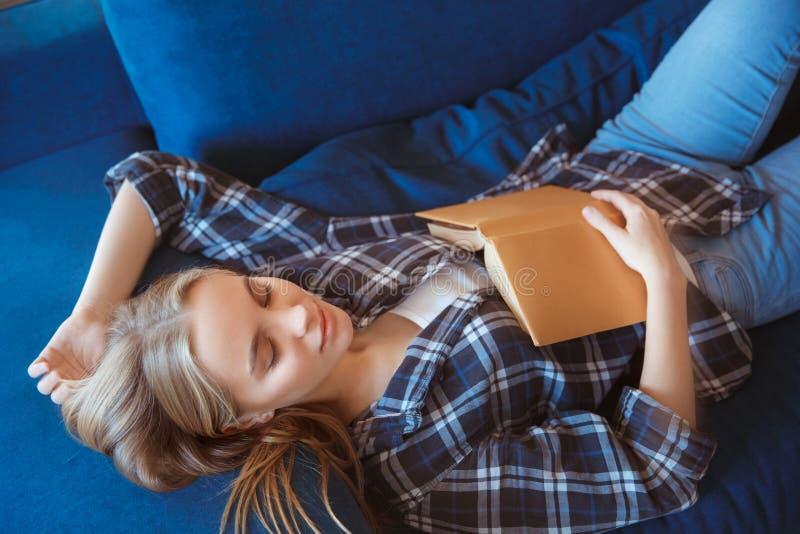 Ung kvinna hemma i vardagsrummet som sover på lagledaren royaltyfri foto