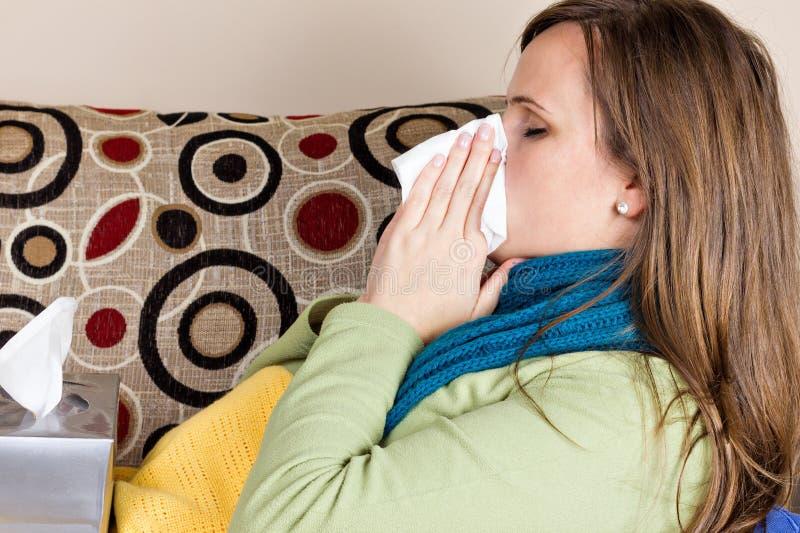 Ung kvinna hemma som har influensa arkivfoton