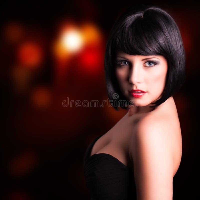 Ung kvinna i aftonkläder framme av en klubbabakgrund royaltyfria foton