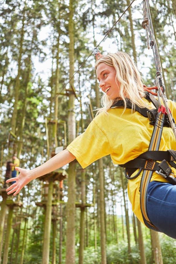 Ung kvinna, i att klättra skogen, medan rappelling arkivbilder