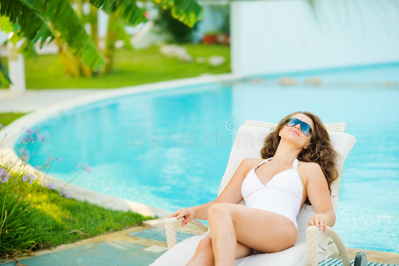 Ung kvinna i avslappnande poolside för baddräkt arkivfoton