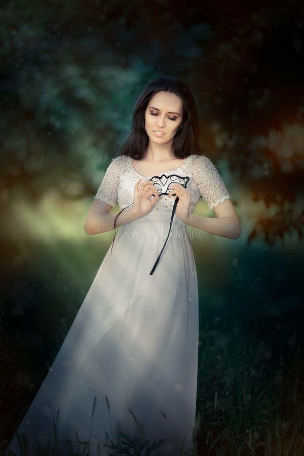 Ung kvinna i bärande maskering för lång vit klänning royaltyfria bilder
