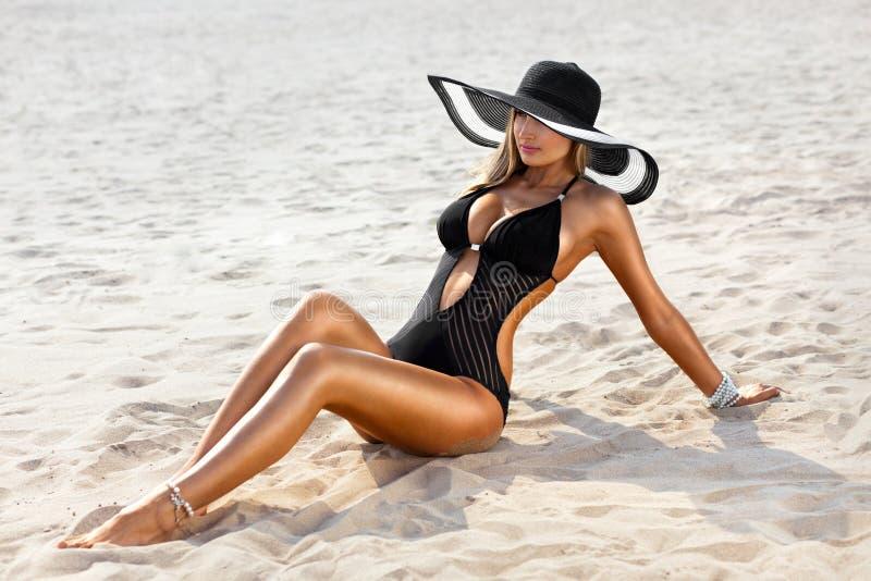 Ung kvinna i baddräkt på stranden arkivbilder