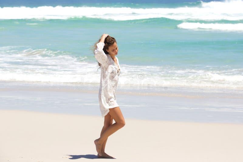 Ung kvinna i begrundande som går på stranden arkivfoton