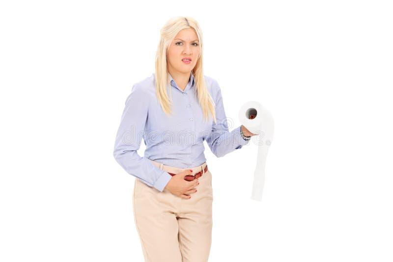Ung kvinna i behov att kissa rymma ett toalettpapper arkivbild