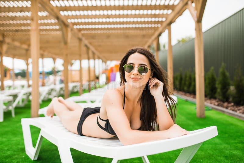 Ung kvinna i bikini, solglasögon och baddräkt som lägger på schäslong och solbadar vid pölen i en sommarsemester royaltyfria foton