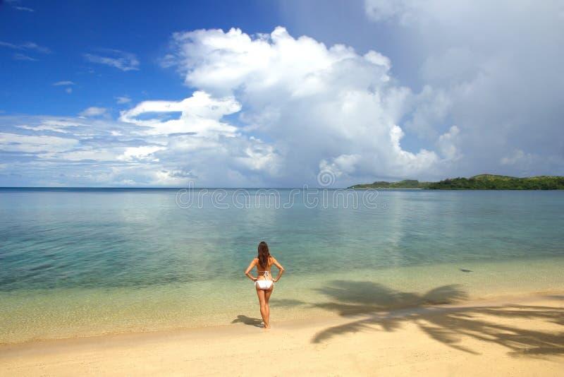 Ung kvinna i bikinianseendet på en tropisk strand, Nananu-jag-rommar arkivbild