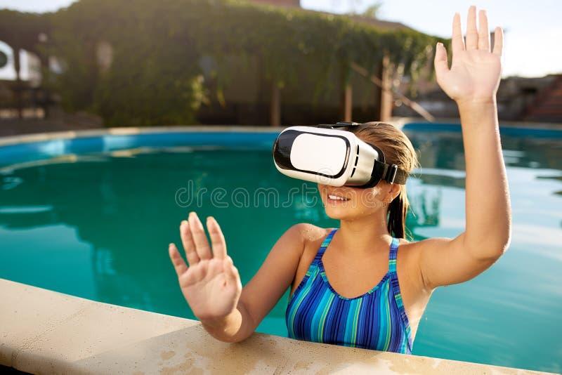 Ung kvinna i bikinibaddräkt genom att använda vattentäta virtuell verklighetexponeringsglas i simbassängen som spelar leken Blond royaltyfria foton