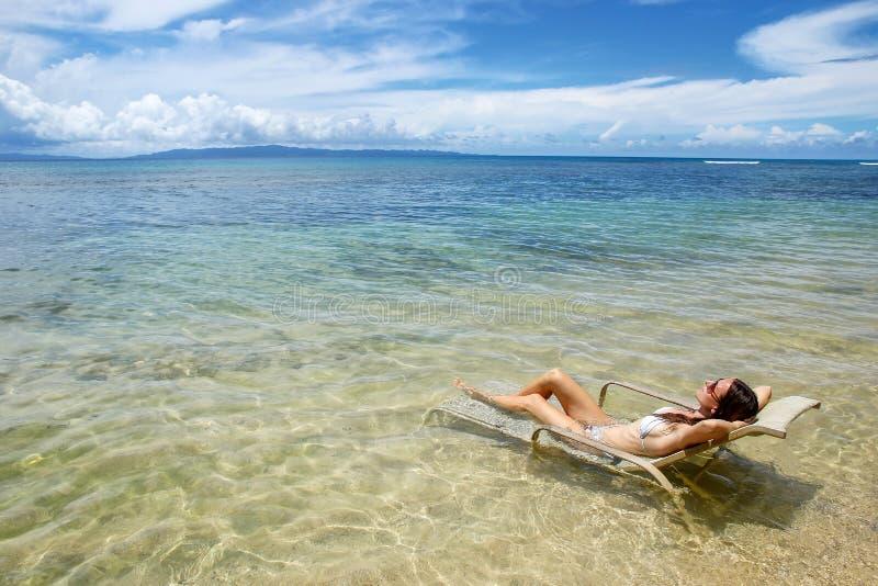 Ung kvinna i bikinin som ligger i en solstol på den Taveuni ön, Fi royaltyfria bilder