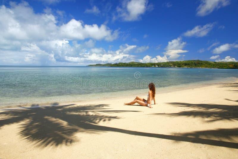 Ung kvinna i bikinisammanträde på en tropisk strand, Nananu-jag-rommar I arkivbilder