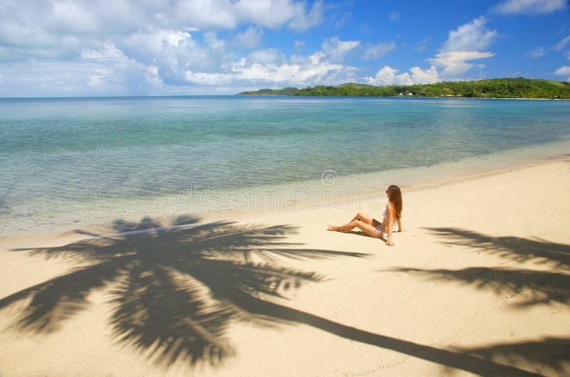 Ung kvinna i bikinisammanträde på en tropisk strand, Nananu-jag-rommar I royaltyfri bild