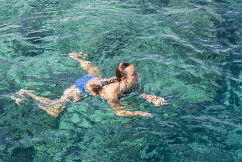 Ung kvinna i bikinisimning i klart vatten Kvinnasimmare som simmar i det blåa havet Kvinnasimning i havet arkivfoto