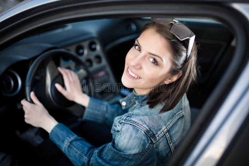 Ung kvinna i bilen som går på vägtur Elevchaufförstudent som kör bilen Körkortexamen royaltyfri foto