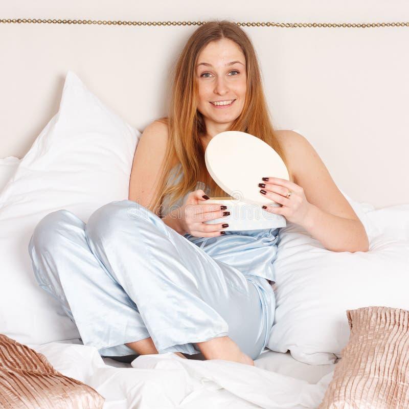 Ung kvinna i blå pyjamas royaltyfri fotografi