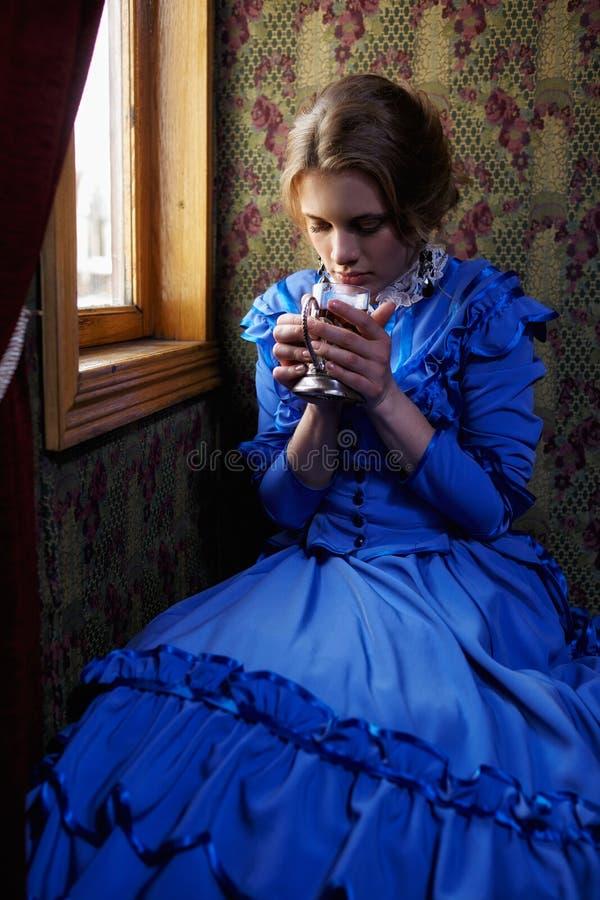 Ung kvinna i blå tappningklänning som dricker te i kupé av retro royaltyfri fotografi